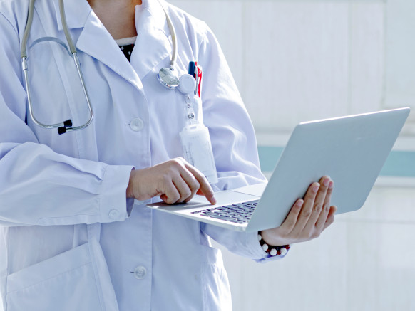 physician using laptop in hospital