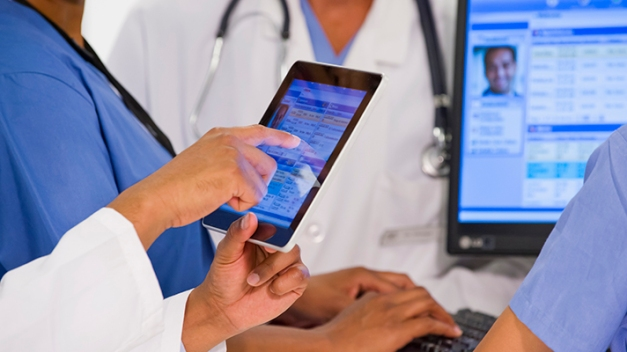 Doctors using digital tablet together in hospital